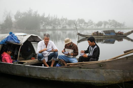 Bourdain enjoys a bite of food while on location in Vietnam
